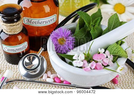 Alternative medicine herbs and stethoscope on wooden table background