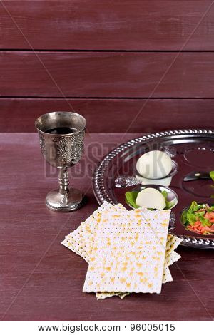 Matzo for Passover with Seder meal with wine on wooden background