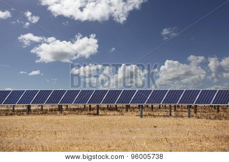 Solar panels with blue sky and clouds.