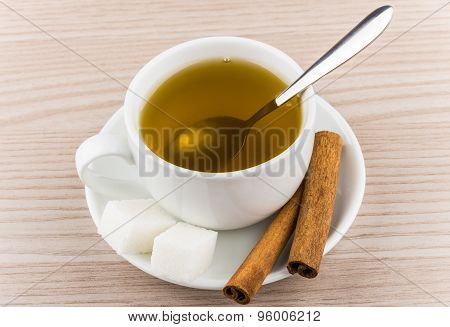 Cup Of Hot Green Tea, Sugar Cubes And Cinnamon Sticks