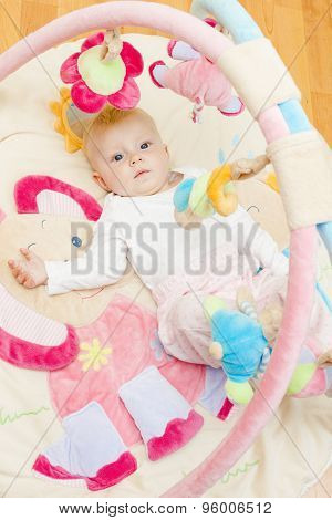 baby girl lying on playing mat