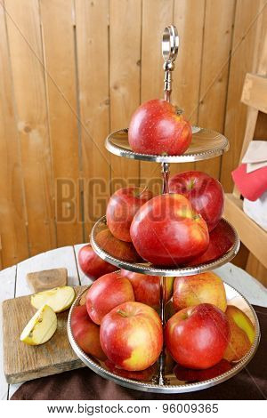 Tasty ripe apples on serving tray on table on wooden background