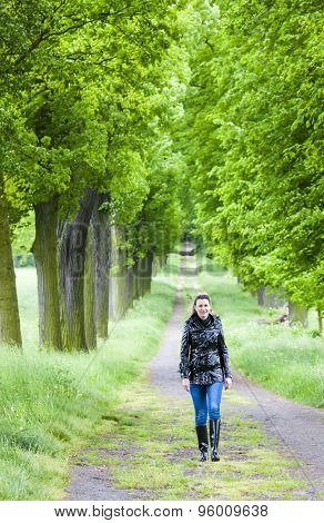woman wearing rubber boots walking in spring alley