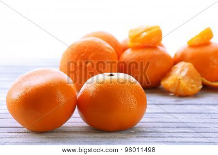 Ripe tangerines on wooden table isolated on white