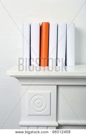 Blank books and orange one on shelf on white wallpaper background