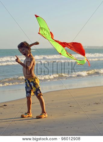 little cute boy with kite playing on seacoast emotional