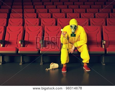 the man in a protective coverall  sitting in an empty theater. Photo combination creative concept