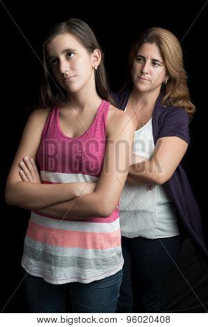 Angry mother with her teenage daughter ignoring her isolated on black