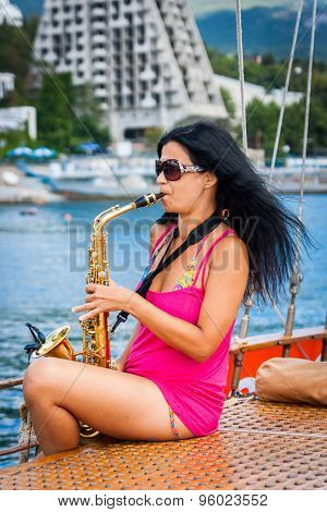 Girl Playing The Saxophone On A Yacht In Sea