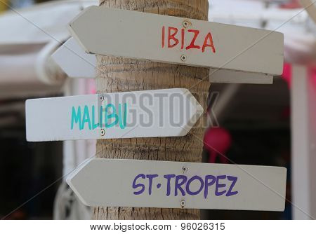 Signpost at the beach indicating popular tourist destinations