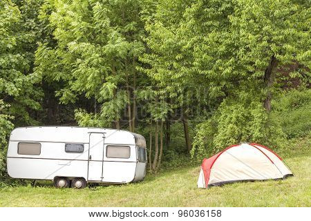 Old Camping Trailer And Tent In The Forest.