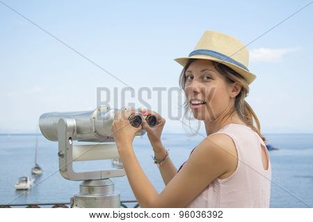 Girl Holding Public Binoculars At The Seaside Wearing Pink Dress And Straw Hat