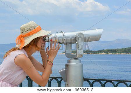 Girl Looking Thru Public Binoculars At The Seaside Wearing Pink Dress And Straw Hat