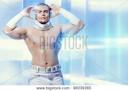 Technologies of the future, man of the future. Handsome muscular man with futuristic make-up in the headphones standing on a luminous transparent background.