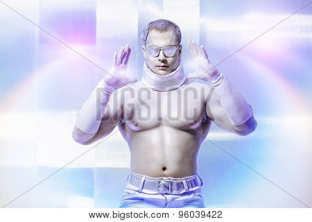 Technologies of the future, man of the future. Handsome muscular man with futuristic make-up wearing glasses stands on a luminous transparent background and touches something virtual.
