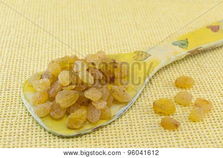 Raisins  In A Decoupage Decorated Spoon On Yellow Background