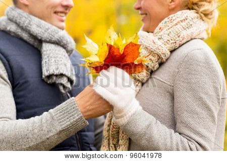 love, relationship, family and people concept - close up of happy smiling couple with maple leaves in autumn park