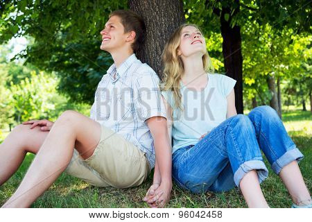 Young beautiful couple resting under a tree