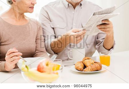 family, mass media, news and people concept - close up of happy senior couple having breakfast and reading newspaper at home