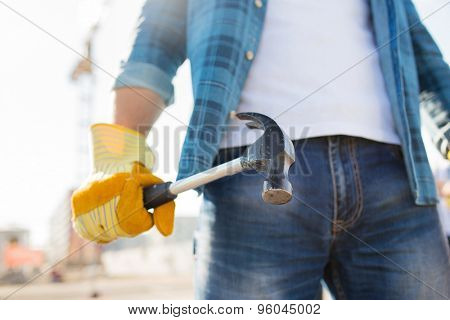 building, tools, construction and people concept - close up of builder hand in glove holding hammer