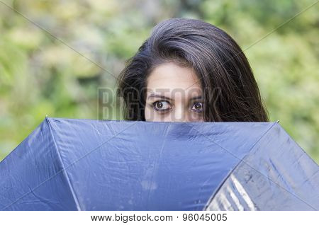 Closeup good-looking hispanic brunette woman head peeking up from behind black umbrella revealing on