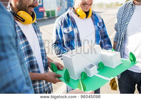 building, construction, teamwork and people concept - close up of smiling builders with paper house model or layout outdoors