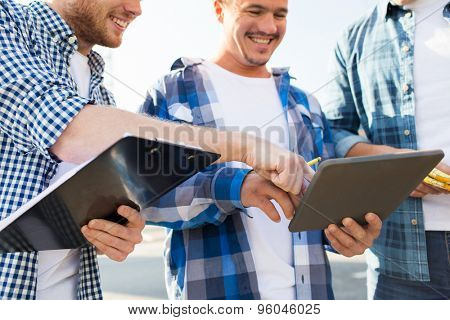 building, construction, teamwork, technology and people concept - group of smiling builders in hardhats with tablet pc computer and clipboard outdoors