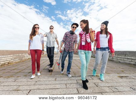 summer holidays and teenage concept - group of teenagers with skates outside