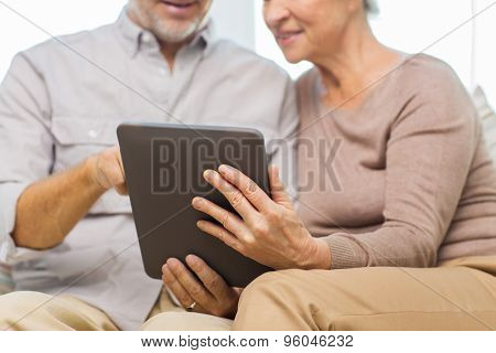 family, technology, age and people concept - close up of happy senior couple with tablet pc computer at home