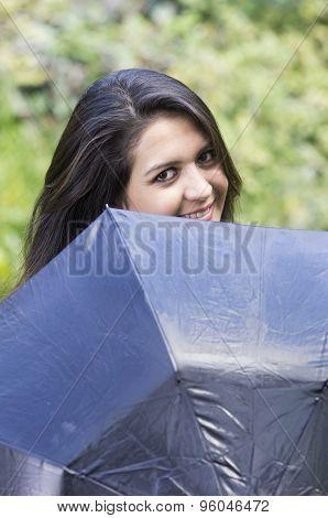 Hispanic good-looking brunette woman head peeking up from behind black umbrella smiling to camera wi