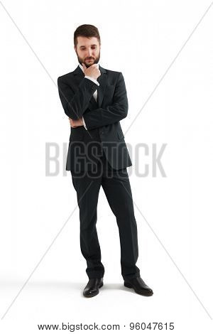serious thoughtful businessman in formal wear holding his hand at chin and looking down. isolated on white background