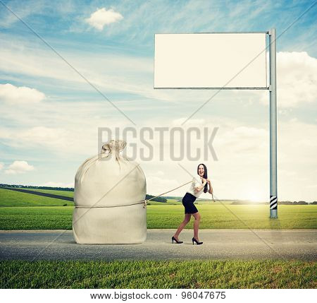 laughing woman pulling big bag on the road against empty billboard