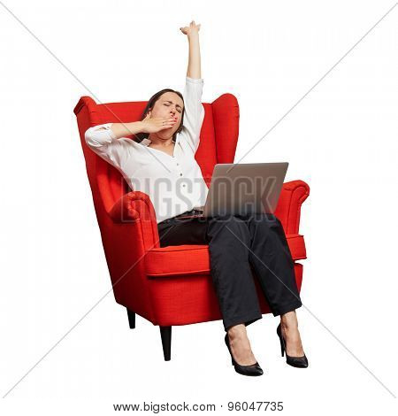tired businesswoman sitting in red chair with laptop and yawning. isolated on white background