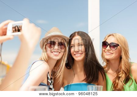 summer holidays and vacation concept - smiling girls taking photo with digital camera in cafe on the beach