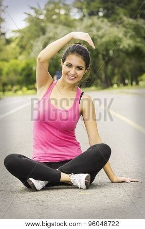 Hispanic brunette in yoga clothing facing camera sitting with legs crossed and stretching right arm