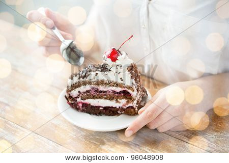 food, junk-food, culinary, baking and holidays concept - close up of woman eating chocolate cherry cake with spoon and sitting at wooden table over holidays lights background
