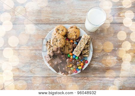 junk food, sweets and unhealthy eating concept - close up of candies, chocolate, muesli bars and cookies with milk glass on plate over holidays lights background