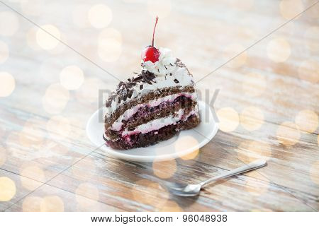 food, junk-food, culinary, baking and holidays concept - piece of delicious cherry chocolate layer cake on saucer with spoon on wooden table over holidays lights background