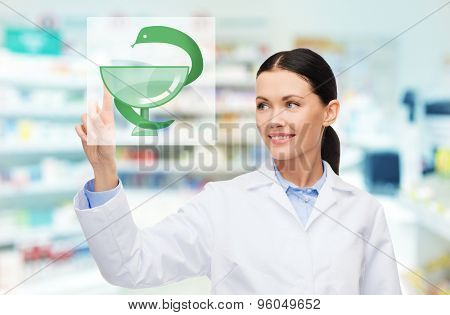 medicine, pharmacy, people, health care and pharmacology concept - happy young woman pharmacist with medical symbol of snake and cup over drugstore background