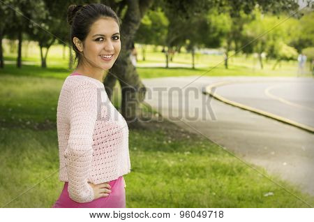 Hispanic brunette wearing yoga clothing in park environment standing on grass looking to camera from