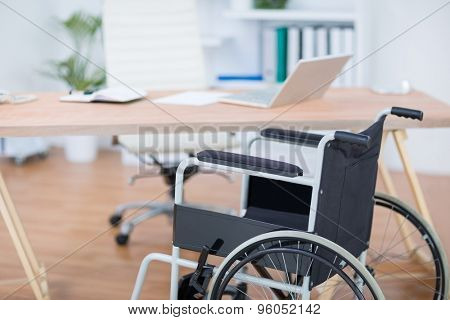 A free wheelchair at his desk in the office