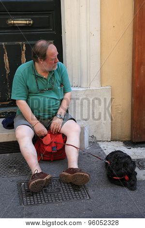 Aix-en-provence, France - July 1, 2014. Elderly Man With A Dog Sitting On The Steps Outside. Aix-en-