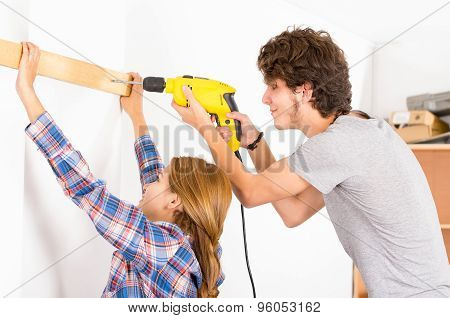 Couple renovating together as man using power drill on wood part and woman helping out by holding