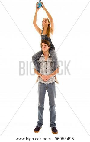 Woman sitting on mans shoulders while she assembles a blue lightbulb high up and he looks forward wi
