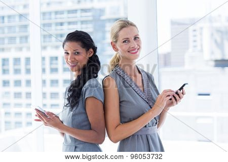 Portrait of back to back businesswomen texting messages