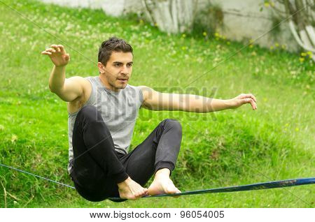 Man sitting on slackline arms to the side concentrating keeping balance with grassy background