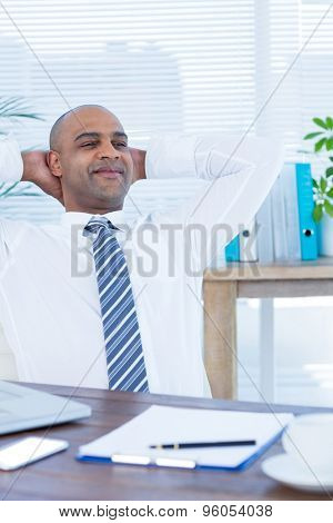 Relaxed businessman lying down in swivel chair at office