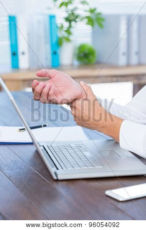 Close up view of man massaging his wrist over a laptop
