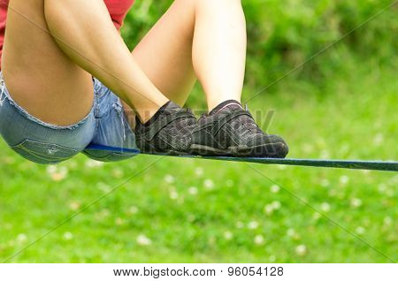 Closeup of womans legs spread out with shoes sitting on slackline and grassy background