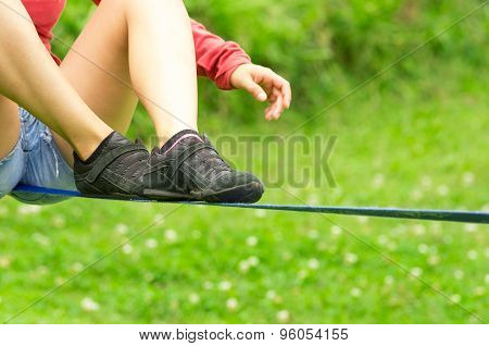 Closeup of womans legs with shoes sitting on slackline and grassy background